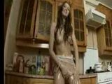 Naked oiled girl masturbating with red toy in the kitchen