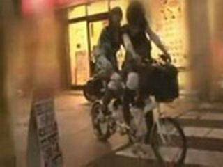 Two Japanese Girls Riding Special Bike Through Downtown