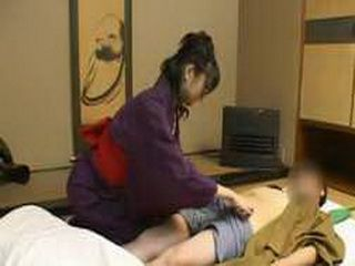 A comely Japanese beauty gives a caring CFNM handjob